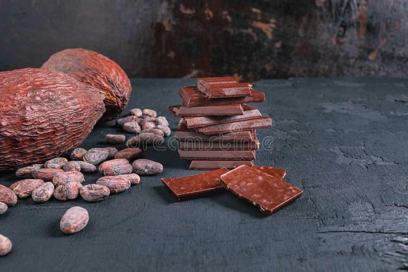 Morceaux de chocolat et graines de cacao foncés sur la table photos libres de droits