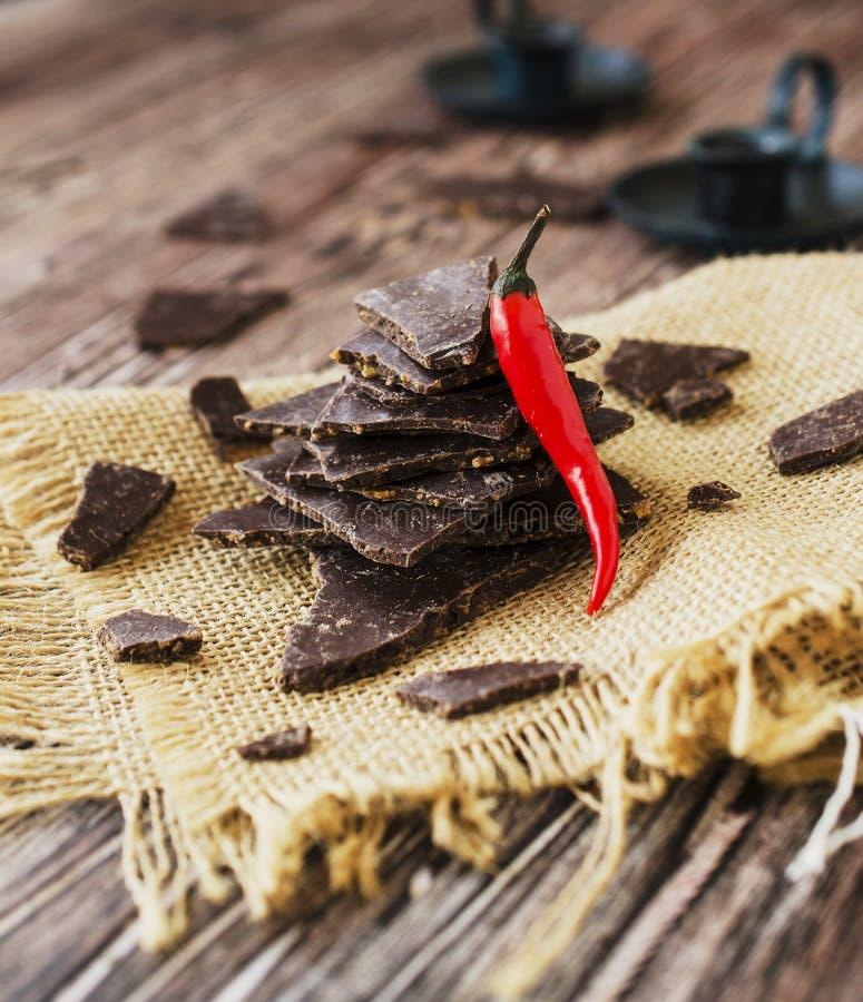 Morceaux de chocolat foncé avec des piments sur le Coal Board noir images libres de droits