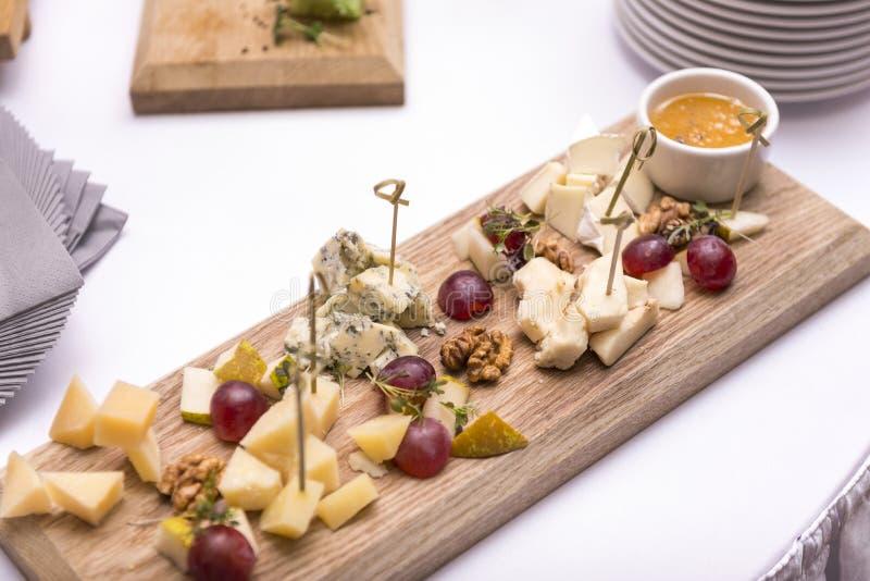 Morceaux de différents types de fromage avec les écrous de raisin et la sauce sur un conseil en bois, plat de fromage photo libre de droits