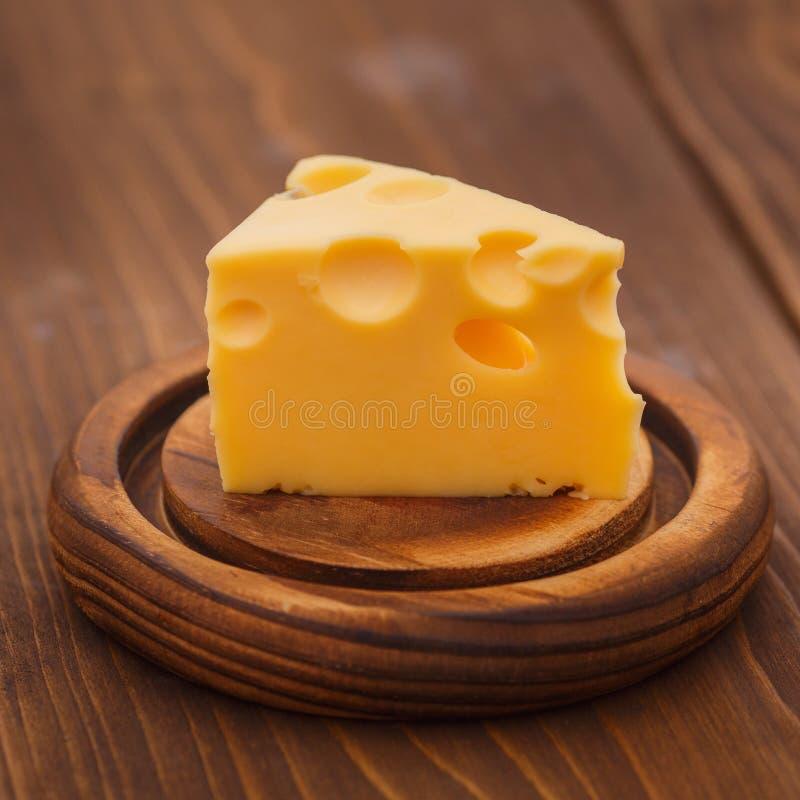 Morceaux de fromage savoureux avec de grands trous sur le bois image libre de droits