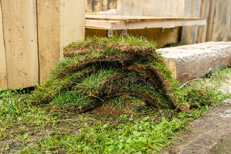 Morceaux de gazon sur le fond des structures en bois images stock