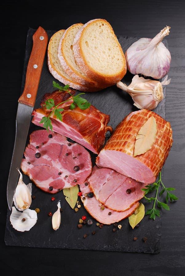 Morceaux de jambon fumé fait maison de porc sur le fond noir images stock