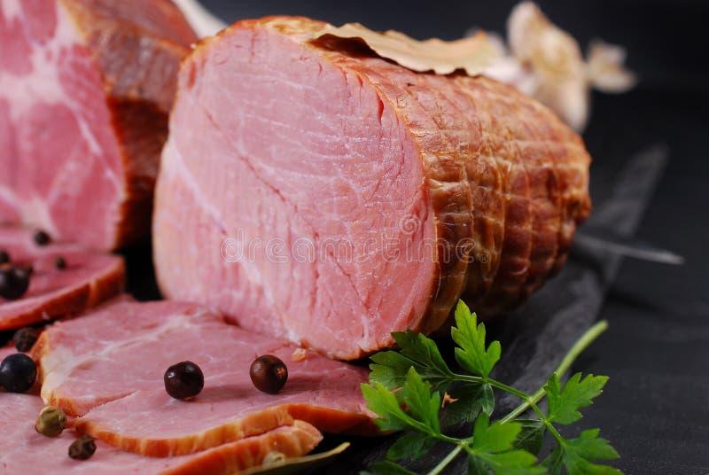 Morceaux de jambon fumé fait maison de porc sur le fond noir photographie stock libre de droits