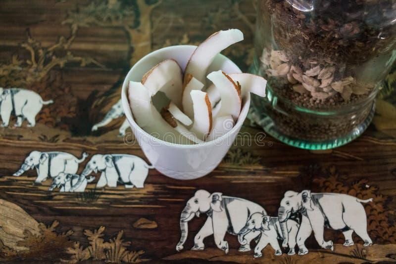 Morceaux de noix de coco dans la tasse image stock