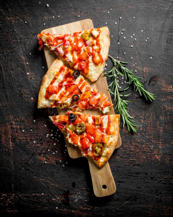 Morceaux de pizza mexicaine sur une planche ? d?couper en bois avec le romarin images libres de droits