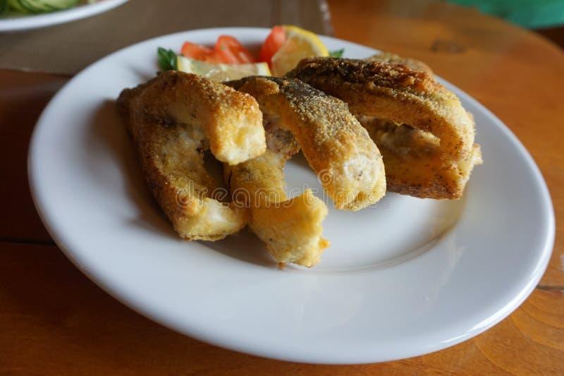 Morceaux de poissons frits d'un plat de porcelaine images libres de droits