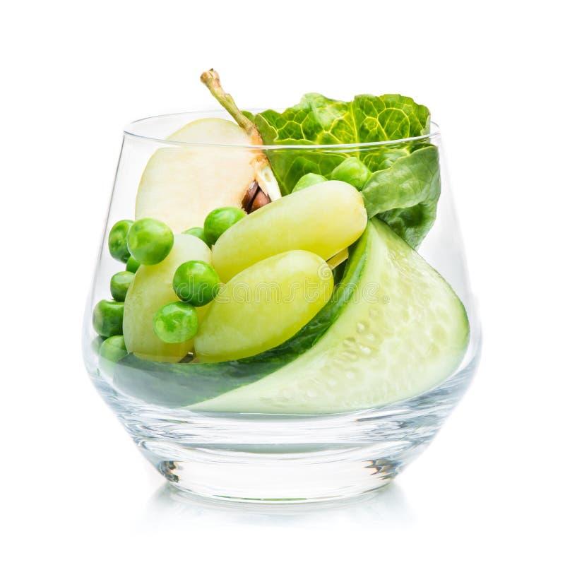 Morceaux de pomme, de raisins et de concombre dans un verre photos libres de droits