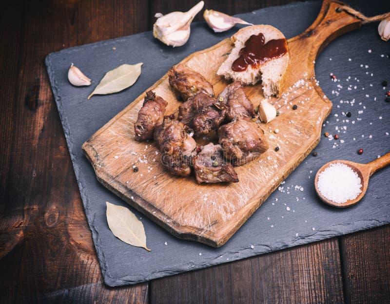 Morceaux de porc frit sur un conseil en bois brun avec des épices photos libres de droits