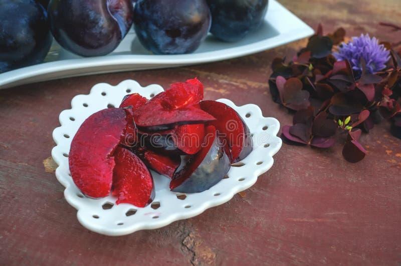 Morceaux de prune rouge juteuse mûre d'un plat blanc sur un fond en bois Foyer sélectif Copiez l'espace photographie stock libre de droits
