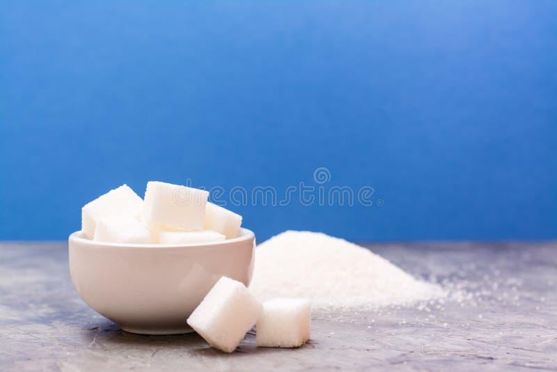 Morceaux de sucre raffiné dans une cuvette et prochain, une pile du sable de sucre images stock