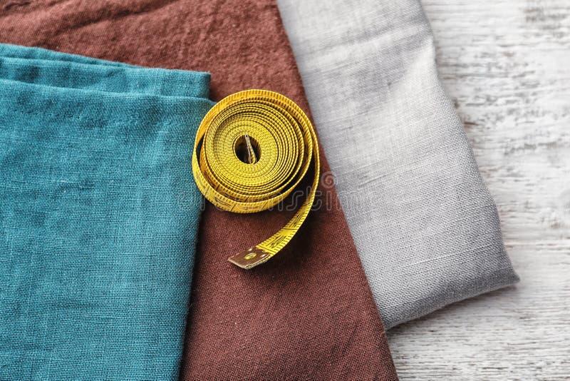 Morceaux de tissu et de bande de mesure sur le fond en bois photo libre de droits
