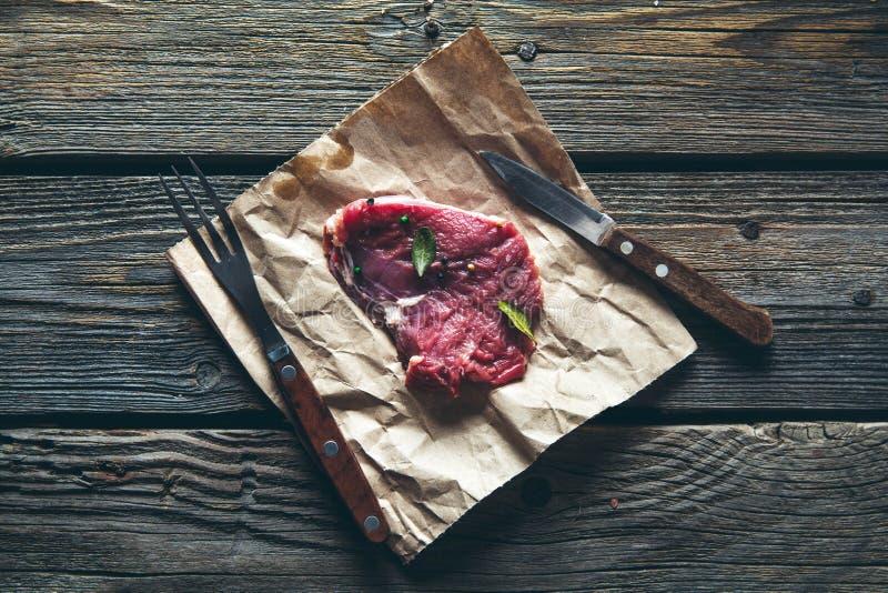 Morceaux de viande, bifteck avec des épices sur un fond en bois Nourriture photos libres de droits