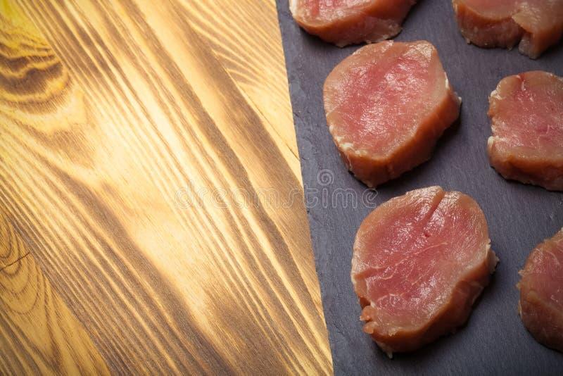 Morceaux de viande crue d'un plat d'ardoise sur un nouveau Ba en bois brûlé photographie stock libre de droits
