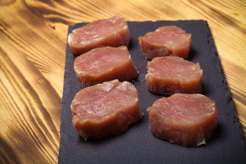 Morceaux de viande crue d'un plat d'ardoise sur un nouveau Ba en bois brûlé image libre de droits