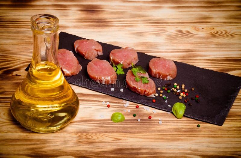 Morceaux de viande crue d'un plat des épices d'herbes d'ardoise et d'oi olive photographie stock libre de droits