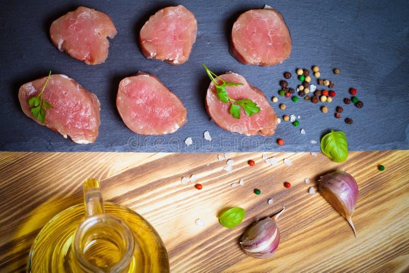 Morceaux de viande crue d'un plat des épices d'herbes d'ardoise et d'oi olive photos libres de droits