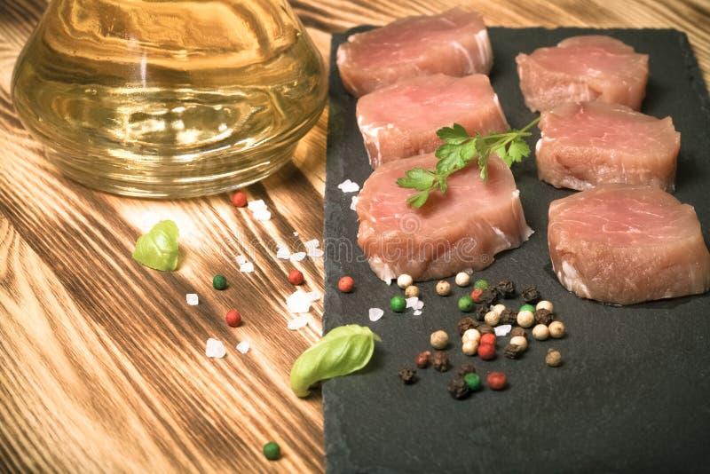 Morceaux de viande crue d'un plat des épices d'herbes d'ardoise et d'oi olive photos stock