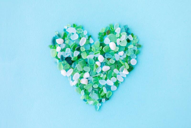 morceaux en verre de mer sous forme de coeur sur le fond bleu photographie stock libre de droits