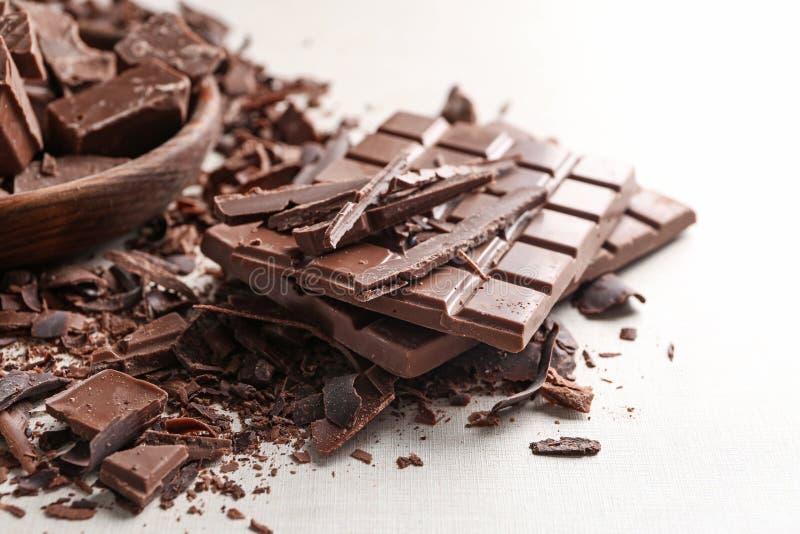 Morceaux et barres de chocolat sur la table photos stock