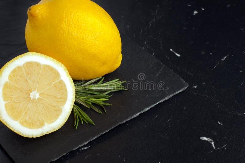Morceaux juteux de citron sur un conseil de marbre noir photos stock
