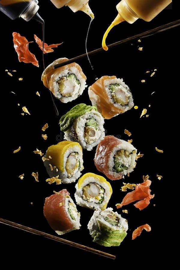 Morceaux volants de sushi avec les baguettes et la sauce en bois, d'isolement sur le fond noir Nourriture de vol et concept de mo photos stock