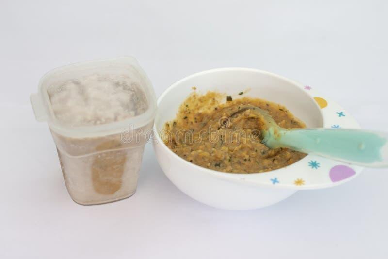 Morcellement de nourriture jusqu'à l'amende pour des bébés dans la cuvette avec la cuillère photographie stock