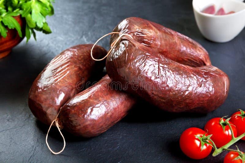 Morcilla fresca cruda con perejil y el tomate cerdo crudo con los tomates de cereza imagen de archivo libre de regalías