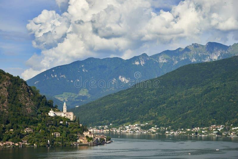 Morcote Schweiz - Juni 4, 2017: Sikt över sjön Lugano till staden Morcote i Ticino, Schweiz och kyrkan av Santa Maria de royaltyfri foto