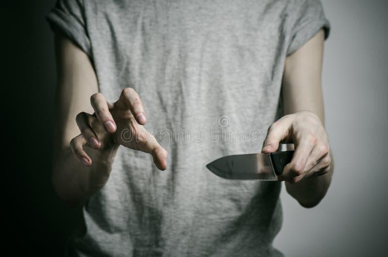 Mord- och allhelgonaaftontema: en man som rymmer en kniv på en grå bakgrund fotografering för bildbyråer