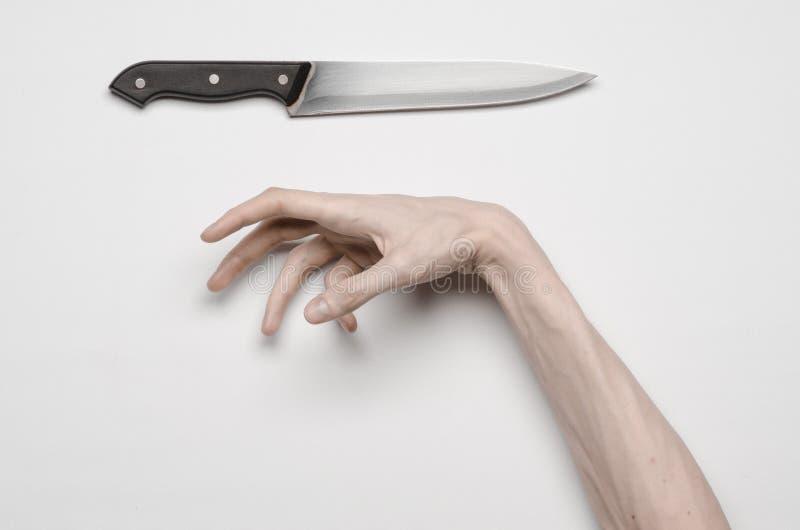 Mord- och allhelgonaaftontema: En mans hand som når för en kniv, en mänsklig hand som rymmer en kniv isolerad på en grå bakgrund  arkivfoton