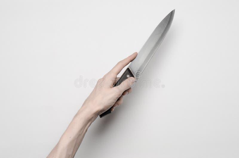 Mord- och allhelgonaaftontema: En mans hand som når för en kniv, en mänsklig hand som rymmer en kniv isolerad på en grå bakgrund  arkivfoto