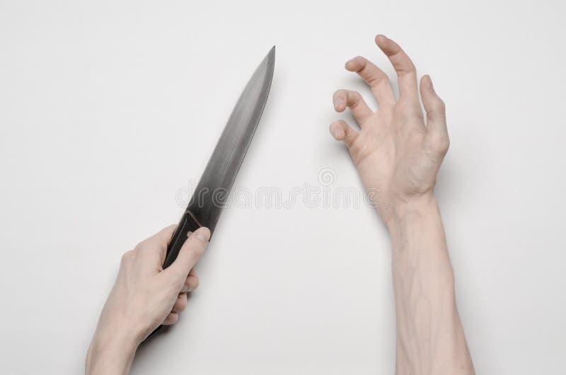 Mord- och allhelgonaaftontema: En mans hand som når för en kniv, en mänsklig hand som rymmer en kniv isolerad på en grå bakgrund  arkivbilder