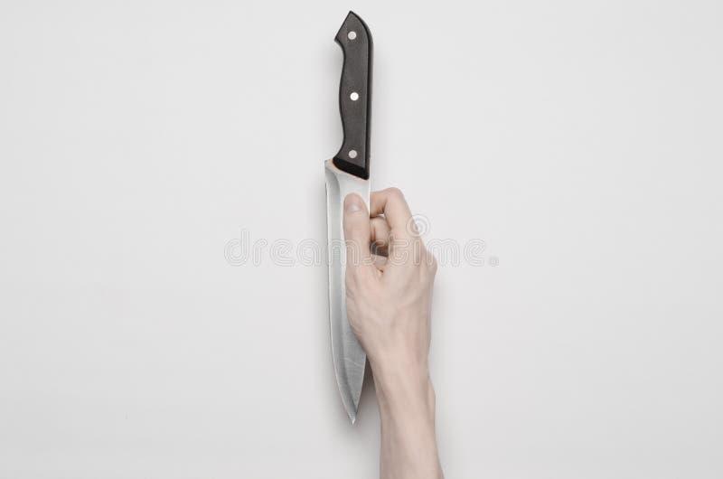 Mord- und Halloween-Thema: Die Hand eines Mannes, die für ein Messer, eine menschliche Hand hält ein Messer lokalisiert auf einem stockfoto