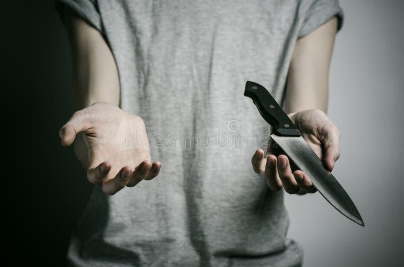 Mord- und Halloween-Thema: ein Mann, der ein Messer auf einem grauen Hintergrund hält lizenzfreies stockfoto