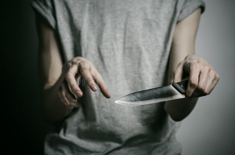 Mord- und Halloween-Thema: ein Mann, der ein Messer auf einem grauen Hintergrund hält stockbild