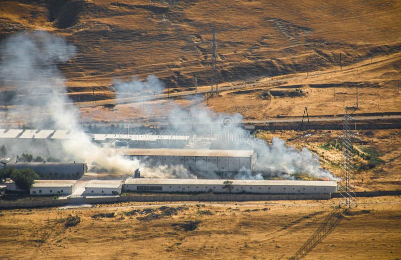 Mordbrand av det industriella lagret, stort rökmoln som fördelar med vind Massiv skada på det företagsbyggnad eller lagret som öv royaltyfria foton