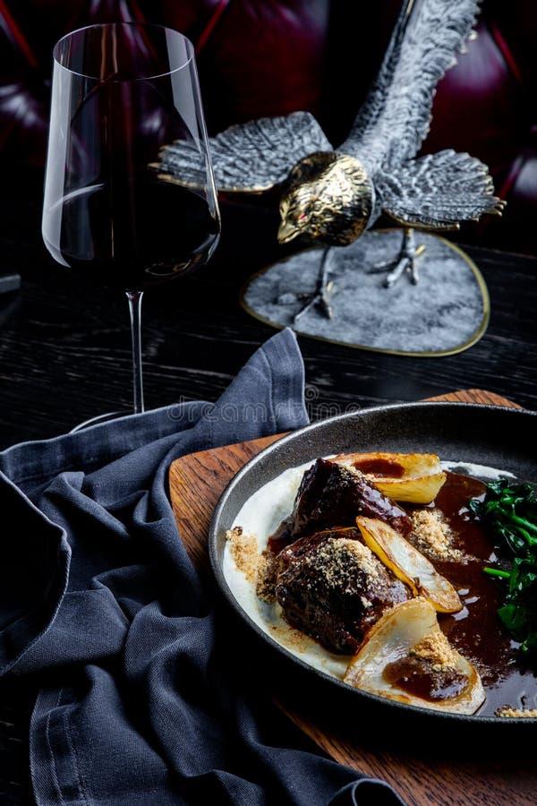 Mordentes cozidos da vitela no vinho tinto, servido com batata triturada Foto para o menu imagens de stock royalty free