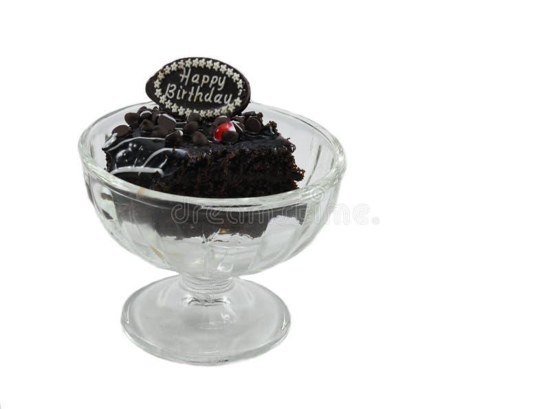 Mordida saboroso dos pedaços de chocolate do bolo de aniversário no vidro do gelado isolado no fundo branco fotografia de stock