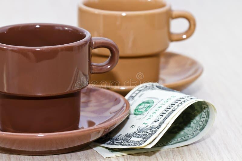 Mordido do dinheiro que encontra-se sob um copo de café vazio imagem de stock royalty free