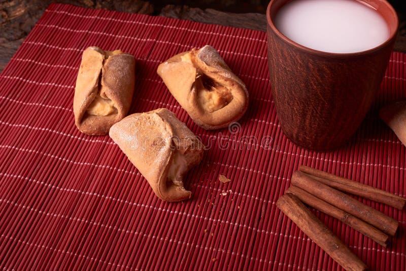 mordiscado na parte das cookies do requeijão coram o cozimento e o vidro da argila do leite na tabela de madeira cookies doces e  fotografia de stock royalty free