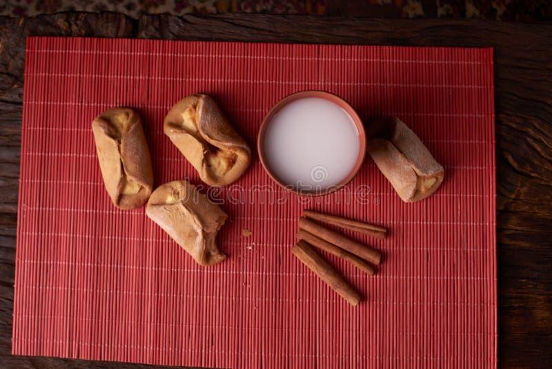 mordiscado na parte das cookies do requeijão coram o cozimento e o vidro da argila do leite na tabela de madeira cookies doces e  fotos de stock royalty free