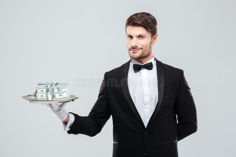 Mordomo lindo no smoking que está e que guarda a bandeja com dinheiro imagens de stock royalty free