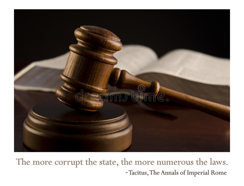 The more corrupt the state... A judge's gavel in the foreground with legal books in the background. An Imperial Rome quote The more corrupt the state, the more stock images