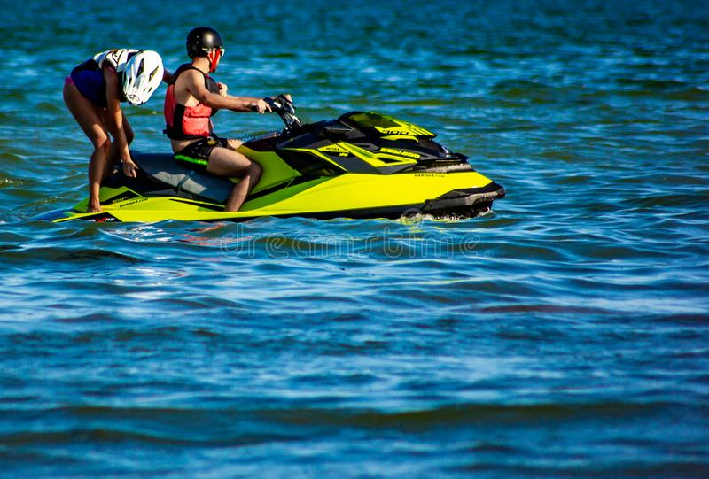 more and more beaches are equipped to rent water scooters. here two guys take a ride with one of these yellow scooters stock images