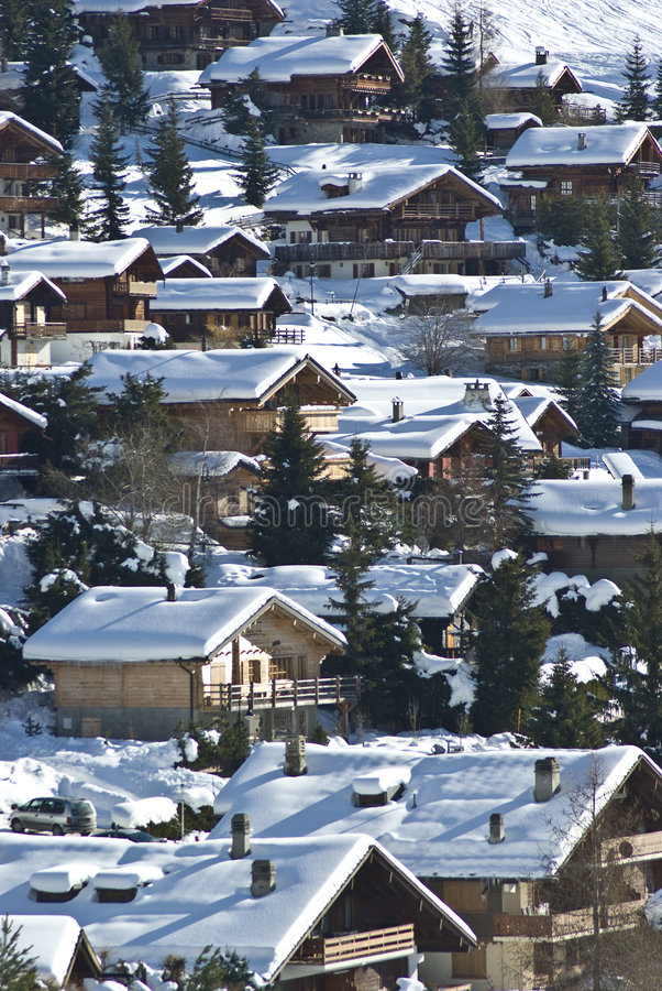 More mountain village chalets. View of verbier in the swiss alps on perfect crisp winters day, perspective compression from extreme telephoto lens stock images