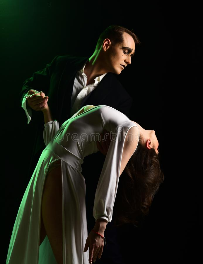 More than a little romance. Theatre actors miming through body motions. Couple of mime artists perform romance on stage. Couple in love with mime makeup. Mime royalty free stock photo