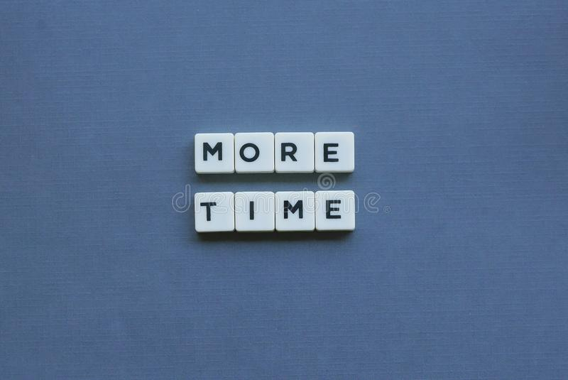 ' More Time ' word made of square letter word on grey background. Message, interlude, persist, motivational, allotment, direction, notice, respite stock photography