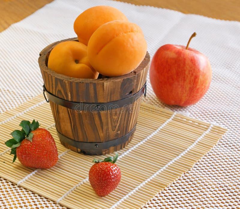 Morele, truskawki, jabłko na białym tle fotografia stock