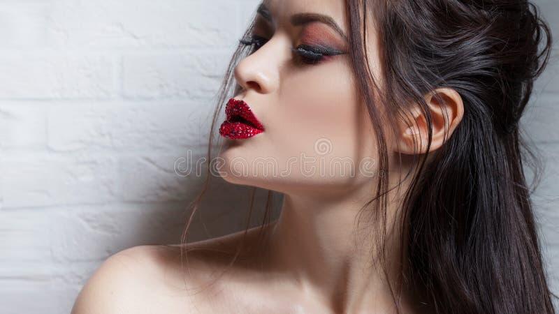 Morena à moda e elegante no preto no fundo branco, retrato no estúdio imagem de stock