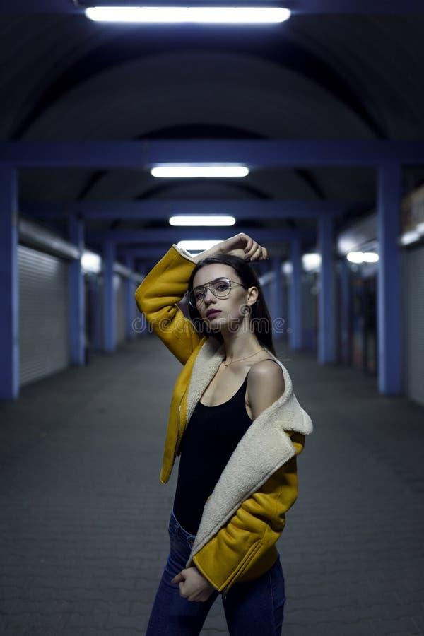 Morena à moda no revestimento amarelo, nas calças de brim e nos vidros para a sessão fotográfica da forma do womenswear Luzes da  fotografia de stock